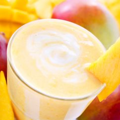 Big glass of fresh mango smoothie with mangos in the background.